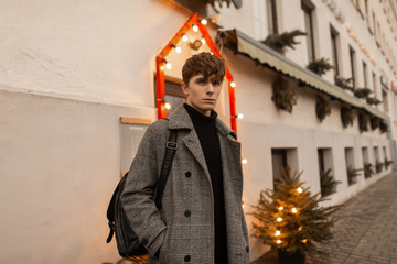 Trendy young man in fashionable winter outerwear stands outdoors in the city near a building decorated with vintage lights and a Christmas tree. Handsome guy in elegant clothes is posing on the street
