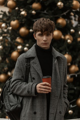 On the background of a vintage Christmas tree is standing a young handsome guy in stylish winter clothes  with a cup of coffee in hands. Attractive guy in youth elegant outerwear outdoors in the city.