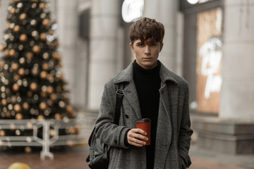 Fashionable handsome young man in a stylish winter outerwear with a trendy hairstyle walks around the city with coffee. Attractive guy travels on the street near a New Year tree and drinks a hot drink