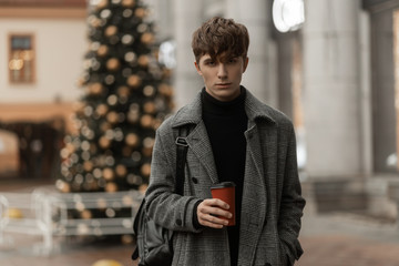 Urban attractive young man is standing in a stylish plaid coat with a trendy hairstyle with a backpack with hot coffee in hands outdoors. Handsome guy model walks around the city in Christmas weekend.