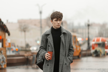 Model of a fashionable young man in an elegant youth checkered coat with a trendy hairstyle stands in the city square with a hot tasty drink in hands. Urban guy walks outdoors and drinks sweet tea.