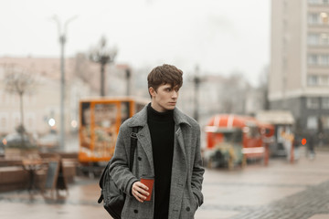 Stylish modern young man stands at a city fair with a hot cafe. Attractive guy fashion model in fashionable winter outerwear walks down the street and drinks a delicious drink.