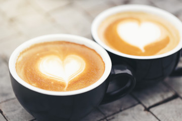 Two black mugs with a coffee drawn in a heart shape.