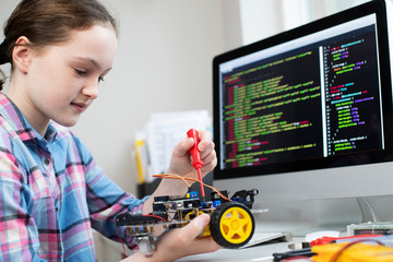 Female Pupil Building Robot Car In School Science Lesson