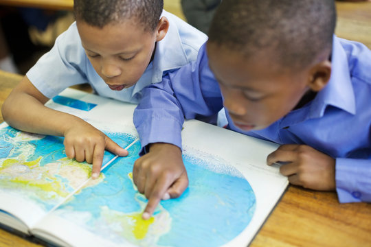 Students using world map in class