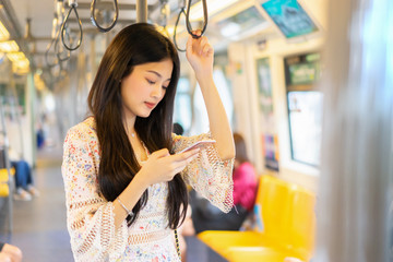 digital travel concept. young Asian woman traveling by the train or Mass Rapid Transit(MRT) train near the window using smartphone in a subway, she texting message and Watching Movie On Mobile Phone