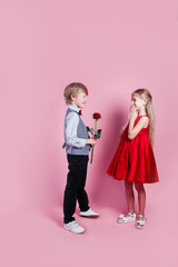 Little boy in love giving cute girl red rose , Valentines day