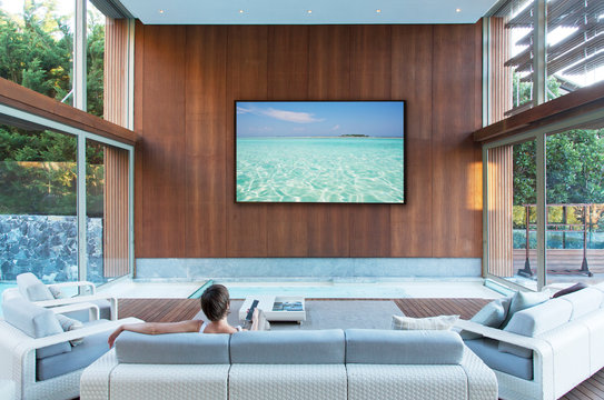 Woman watching large flat screen TV in modern living room