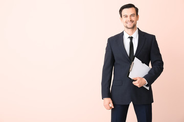 Male real estate agent on color background