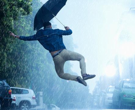 Man with umbrella jumping in rain