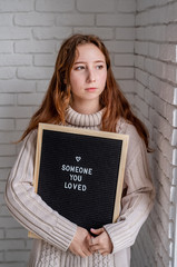 sad beautiful woman holding felt letter board with the words Someone You Loved