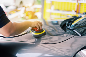 restore detailed cars: Polishing a car, Car care with power buffer machine at a service station,  Man with mechanically polished finishing