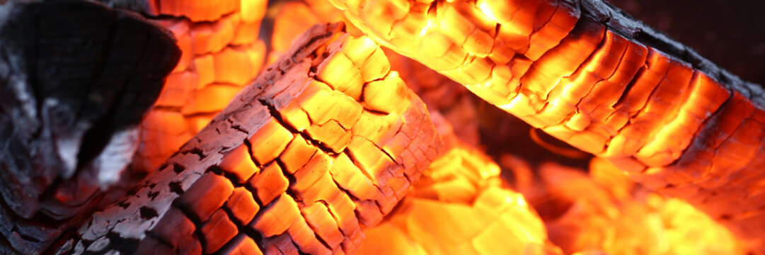 Close-up of burning log in bonfire. Large orange flame from fire with woods. Light and ash from wood in balefire. Amazing campfire with dark view outdoor