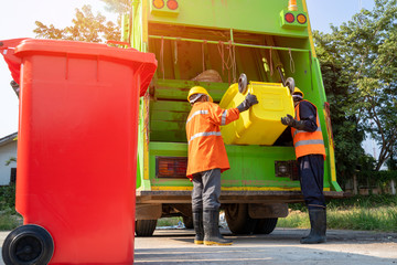 Two garbage men working together on emptying dustbins for trash removal with truck loading waste...