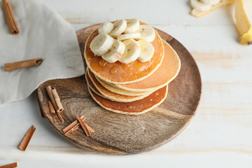 Plate with stack of tasty pancakes on table