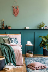 Stylish composition of bedroom interior with wooden bed, design furnitures, shelf, plants, decor...