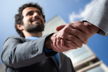 Businessmen shaking hands outdoor in a modern setting