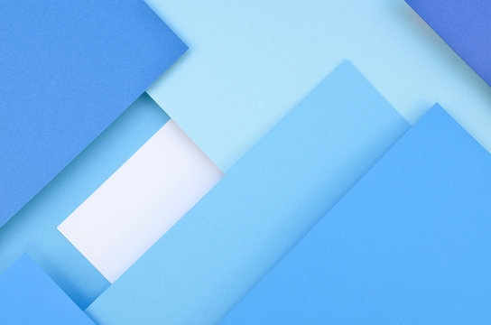 Abstract geometric paper texture background. Parallel ombre blue layers with shadows. Flat lay
