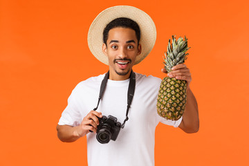 Charismatic young attractive african-american tourist, traveller taking pictures from vacation on camera, holding pineapple and smiling joyfully, having fun on summer luxury resort, orange background