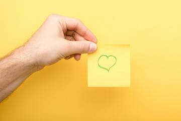 cropped view of man holding sticky note with heart on yellow background