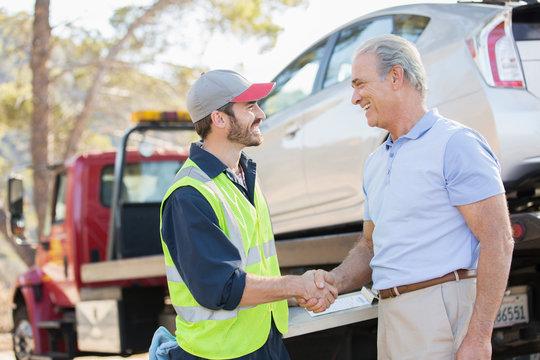 Roadside mechanic and man shaking hands
