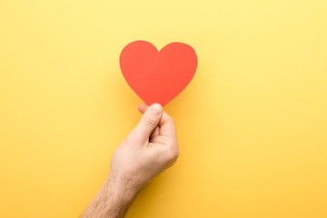 cropped view of man holding heart-shaped card on yellow background