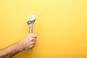 cropped view of man holding spanner on yellow background