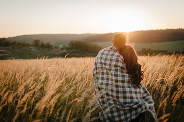 Young couple hugging, standing back, people covered with blanket, at sunset in autumn an outdoor. at field grass on  background of sun. Concept of friendly family. full length. Close Up.