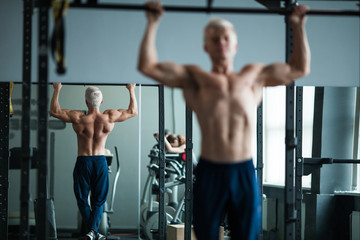 Muscular athlete man making Pull-up in gym. Bodybuilder training in fitness club showing his perfect back and shoulder muscles.