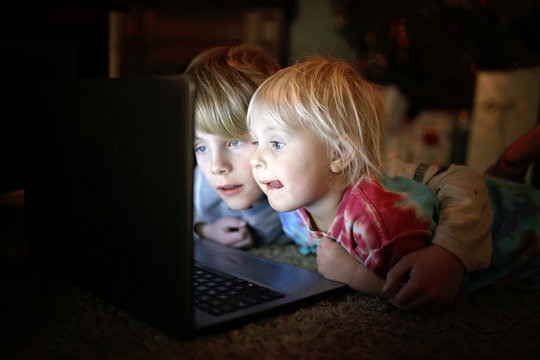 Two Little Children Watching Internet Video on their Laptop Computer