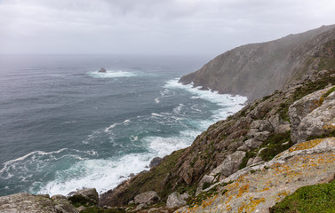 The view of the Atlantic at the end of the long pilgrim route. The cape at the Finisterre lighthouse is covered in haze. The great waves of the ocean meet the wild coast.
