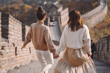 two female friends walking along the Great Wall of China near the Beijing entarnce. Two stylish...