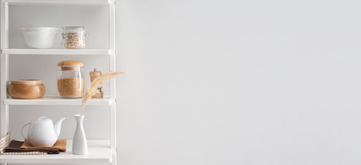 Kitchenware on shelves near white wall with space for text