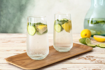 Glasses of cold cucumber water on white table