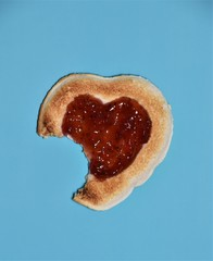 Single white bread toast in heart shape with strawberry jam, isolated on blue background.