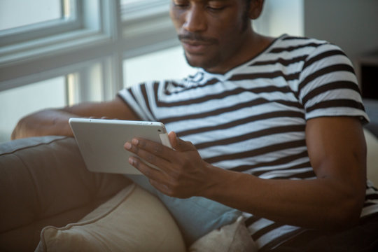 Midsection of man using tablet computer on sofa at home