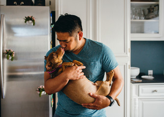 Man kissing puppy while standing at home