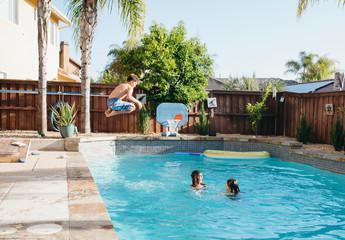 Shirtless boy jumping in swimming pool