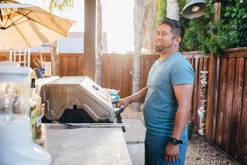 Side view of smiling man looking away while cooking food in yard