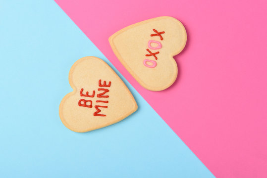 Valentines Day Concept: Two Heart shaped sugar cookies one on pink one on blue with Be Mine and XOXO written in icing.
