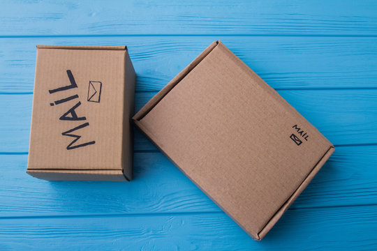 Two cardboard mail boxes, flat lay. Blue wood background.