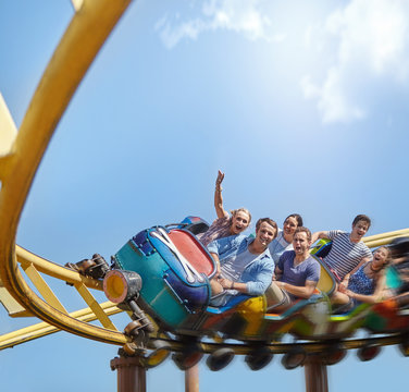 Cheering friends riding roller coaster at amusement park