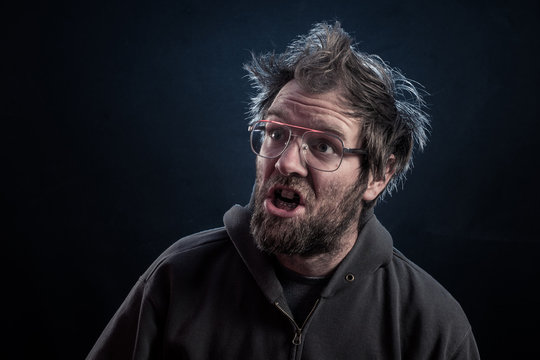 A goofy man with a beard, hipster glasses, rabbit teeth, dental braces on a dark red lit background with brown hoodie or sweater and electrified hair.