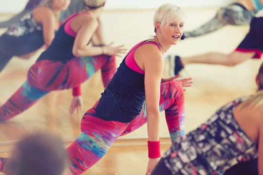 Fitness instructor leading class in lunge