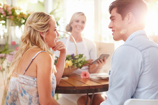 Couple talking with florist in flower shop