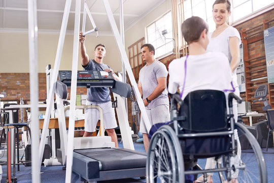 Physical therapists preparing treadmill for man in wheelchair