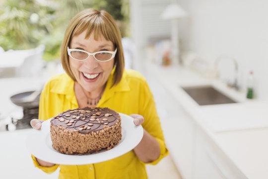Portrait smiling mature woman holding chocolate cake