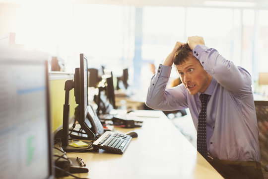 Stressed businessman pulling his hair out at computer in office