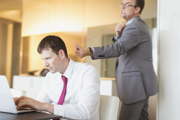Angry businessman aiming rubber bat unsuspecting businessman working at laptop