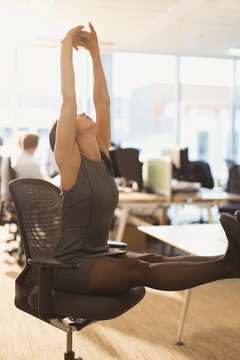 Businesswoman stretching arms overhead with feet up on desk in office